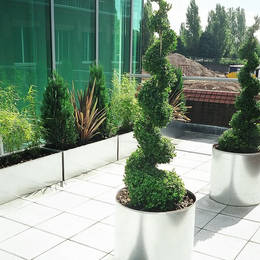 The grey paving slabs on this roof top garden are vastly improved with contemporary exterior landscping from Office Landscapes