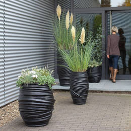 Two different size containers with different types & sizes of planting improve this business exterior